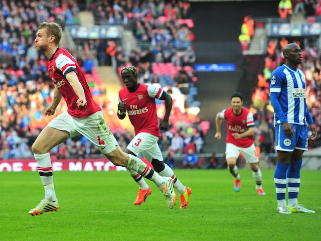 Per Mertesacker of Arsenal wheels away in delight after scoring the equaliser against Wigan Athletic in the FA Cup semi-final at Wembley on April 12, 2014