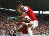 Lukas Podolski of Arsenal celebrates with team mate Olivier Giroud after scoring his sides third goal during the Barclays Premier League match between Hull City and Arsenal at KC Stadium on April 20, 2014