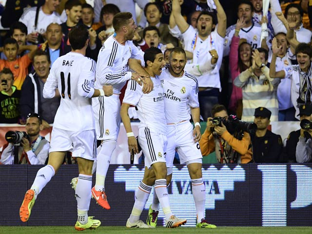 Real's Angel di Maria is congratulated by team mates after scoring the opening goal against Barcelona during the Copa del Rey final match on April 16, 2014