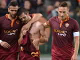 Roma's Miralem Pjanic celebrates with teammates after scoring the opening goal against AC Milan during the Serie A match on April 25, 2014
