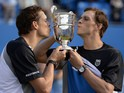 US brothers Bob Bryan and Mike Bryan kiss the trophy after winning the ATP Aegon Championships doubles final at Queen's Club, London on June 16, 2013