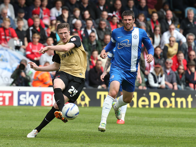 John Lundstram of Leyton Orient plays the ball watched by Michael Bostwick of Peterborough United during the Sky Bet League One Semi Final First Leg between Peterborough United and Leyton Orient at London Road Stadium on May 10, 2014