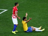 Fred of Brazil gestures for a foul from the ground as Dejan Lovren of Croatia looks on in the second half during the 2014 FIFA World Cup Brazil Group A match between Brazil and Croatia at Arena de Sao Paulo on June 12, 2014