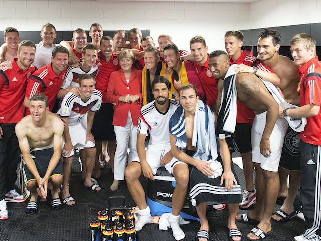 German Chancellor Angela Merkel visits the German National team in their dressing room after the 2014 FIFA World Cup Group G match against Portugal at Arena Fonte Nova on June 16, 2014 in Salvador, Brazil