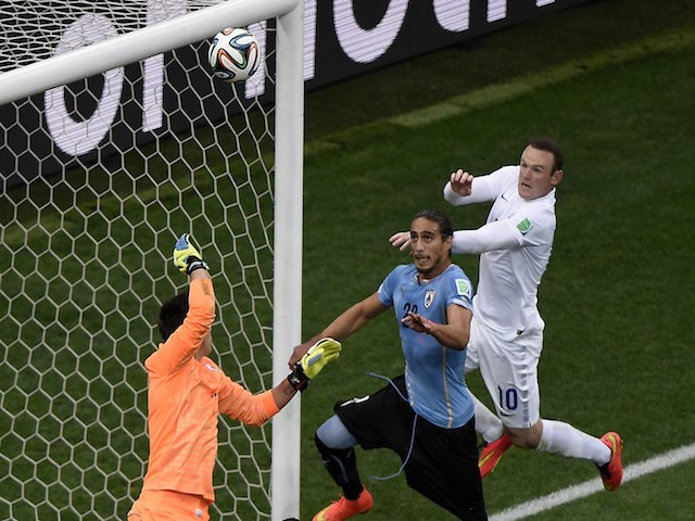 England's forward Wayne Rooney (R) jumps to head the ball during a Group D football match between Uruguay and England at the Corinthians Arena in Sao Paulo during the 2014 FIFA World Cup on June 19, 2014