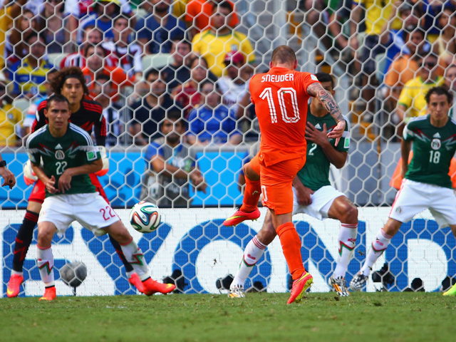 Wesley Sneijder of the Netherlands shoots and scores his team's first goal past Guillermo Ochoa of Mexico during the 2014 FIFA World Cup Brazil Round of 16 match between Netherlands and Mexico at Castelao on June 29, 2014