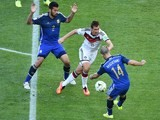 Germany's forward Miroslav Klose (C) tackles Argentina's midfielder Javier Mascherano (R) as Argentina's defender Ezequiel Garay looks on during the final football match on July 13, 2014