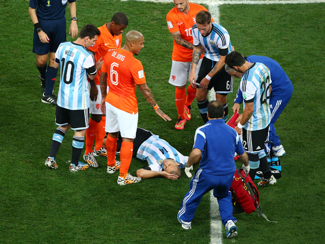 Javier Mascherano of Argentina receives treatment after a collision during the 2014 FIFA World Cup Brazil Semi Final match between the Netherlands and Argentina at Arena de Sao Paulo on July 9, 2014