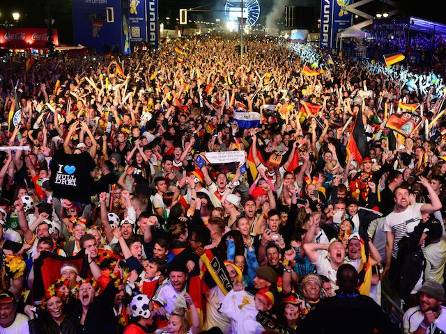 German fans react at the end of the FIFA World Cup 2014 final football match Germany vs Argentina played in Brazil during an outdoor screening near the Brandenburg Gate in Berlin, on July 13, 2014
