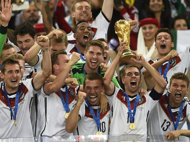 Germany's defender and captain Philipp Lahm (front-R) holds up the World Cup trophy as he celebrates on with his teammates after winning the 2014 FIFA World Cup final on July 13, 2014