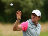 Rory McIlroy of Northern Ireland reaches for a golf ball on the practice ground during the final round of The 143rd Open Championship at Royal Liverpool on July 20, 2014 in Hoylake, England