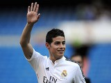 James Rodriguez waves to fans during his unveiling as a new Real Madrid player at the Santaigo Bernabeu stadium on July 22, 2014