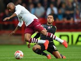 Aston Villa player Fabian Delph is challenged by Billy Clifford of Walsall during the Pre-Season Friendly between Walsall v Aston Villa at Banks' Stadium on August 5, 2014