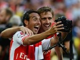 Arsenal teammates Santi Cazorla and Nacho Monreal pose for a selfie with an extremely large camera after winning the Community Shield on August 10, 2014