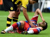 Dortmund's Greek defender Sokratis talks to injured Bayern Munich's Spanish midfielder Javier Martinez during the German Supercup football match Borussia Dortmund vs Bayern Munich in the German city of Dortmund on August 13, 2014