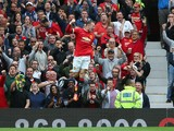 Wayne Rooney of Manchester United celebrates scoring his team's first goal during the Barclays Premier League match between Manchester United and Swansea City at Old Trafford on August 16, 2014
