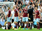 James Collins of West Ham walks off the pitch as referee Chris Foy shows him the the red card for his second bookable offence during the Barclays Premier League match between West Ham United and Tottenham Hotspur at Boleyn Ground on August 16, 2014