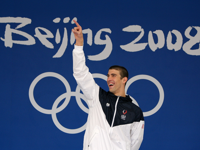Gold medalist Michael Phelps of the United States celebrates on the podium during the medal ceremony for the Men's 100m Butterfly Final held at the National Aquatics Centre during Day 8 of the Beijing 2008 Olympic Games on August 16, 2008