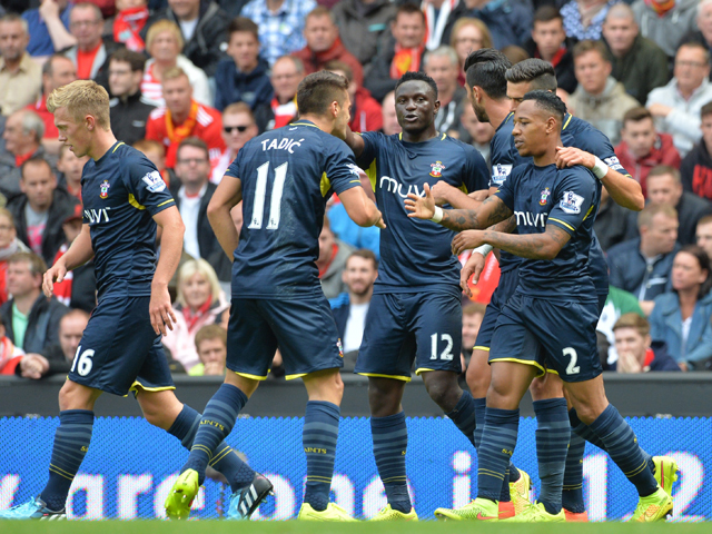 Southampton's English defender Nathaniel Clyne clebrates scoring the equalising goal with teammates during the English Premier League football match between Liverpool and Southampton at Anfield stadium in Liverpool, northwest England, on August 17, 2014