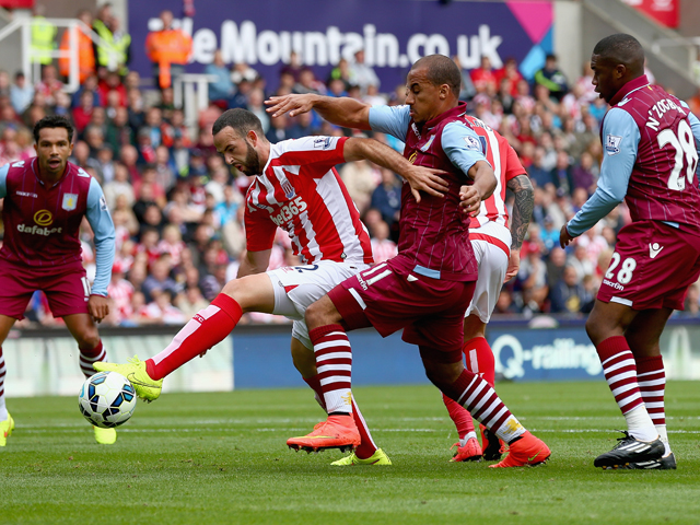 Gabriel Agbonlahor of Aston Villa in action with Marc Wilson of Stoke City during the Barclays Premier League match between Stoke City and Aston Villa at Britannia Stadium on August 16, 2014