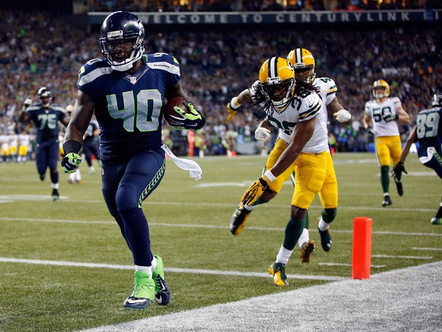 Fullback Derrick Coleman #40 of the Seattle Seahawks scores a touchdown as cornerback Tramon Williams #38 of the Green Bay Packers gives chase during the fourth quarter of the game at CenturyLink Field on September 4, 2014