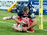 Rob Cook of Gloucester Rugby scores a try in the corner as Tom Brady of Sale Sharks tries to tackle during the Aviva Premiership match between Gloucester Rugby and Sales Sharks at Kingsholm on September 13, 2014