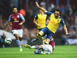 Santi Cazorla of Arsenal is challenged during the Barclays Premier League match between Aston Villa and Arsenal at Villa Park on September 20, 2014