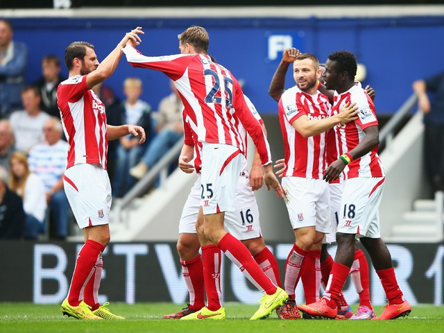Mame Biram Diouf of Stoke City celebrates scoring the opening goal with team mates during the Barclays Premier League match between Queens Park Rangers and Stoke City at Loftus Road on September 20, 2014