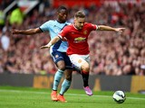 Luke Shaw of Manchester United goes past the challenge from Diafra Sakho of West Ham during the Barclays Premier League match between Manchester United and West Ham United at Old Trafford on September 27, 2014