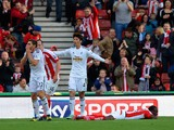 Victor Moses of Stoke City lies in the area as Angel Rangel of Swansea City (L) reacts after conceding a penalty, as Ki Sung-Yueng of Swansea City appeals to the Referee during the Barclays Premier League match between Stoke City and Swansea City at Brita