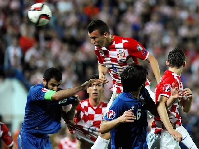 Croatia's midfielder Ivan Perisic (up) scores a goal over Azerbaijan's defenders Rashad Sadygov (L) and Badavi Guseynov (C) during the Euro 2016 group H qualifying football match  on October 13, 2014