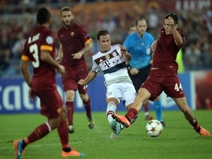 Bayern Munich's midfielder from Germany Mario Goetze (C) kicks to score during the Champions League group stage football match AS Roma vs Bayern Munich on October 21, 2014