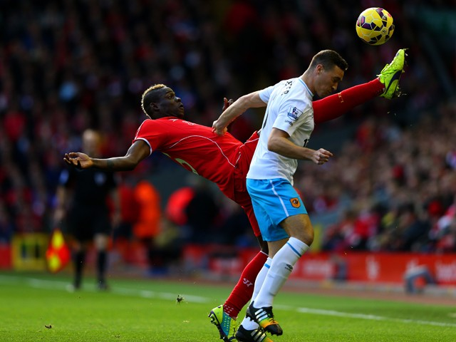 Mario Balotelli of Liverpool is challenged by James Chester of Hull City during the Barclays Premier League match between Liverpool and Hull City at Anfield on October 25, 2014