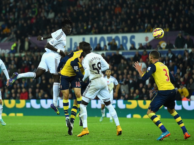 Swansea player Bafetimbi Gomis (c) heads the second Swansea goal during the Barclays Premier League match between Swansea City and Arsenal at Liberty Stadium on November.9, 2014