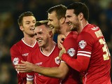 Cardiff player Ben Turner (2nd r) celebrates with team mates after Reading player Alex Pearce had put into his own net for the opening goal on November 21, 2014