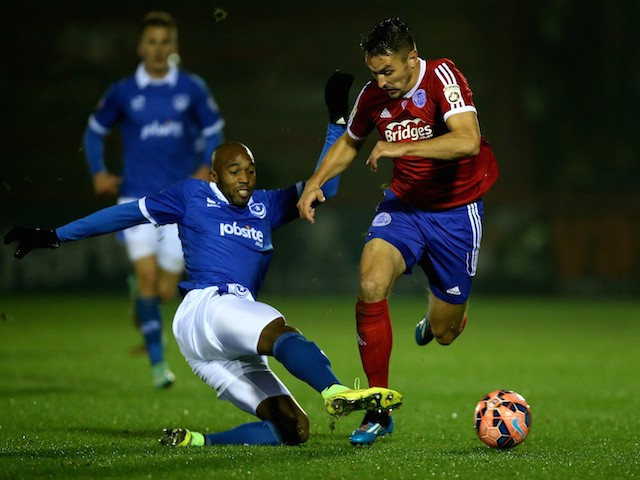 Nigel Atangana of Portsmouth tackles Brett Williams of Aldershot during the FA Cup First Round Replay match on November 19, 2014