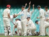 Phil Hughes lies on the ground surrounded by teammat