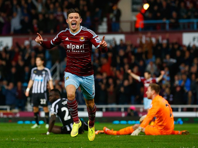 Aaron Cresswell of West Ham celebrates scoring opening goal past Robert Elliot of Newcastle United during the Barclays Premier League match between West Ham United and Newcastle United at Boleyn Ground on November 29, 2014