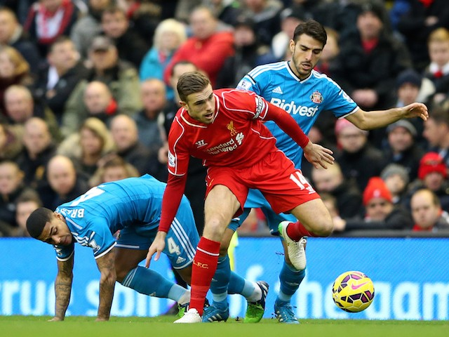 Jordan Henderson of Liverpool battles for the ball with Jordi Gomez and Liam Bridcutt of Sunderland during the Barclays Premier League match on December 6, 2014