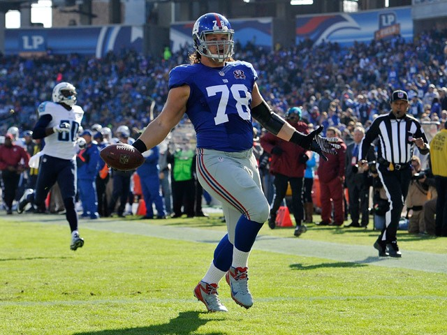 Markus Kuhn #78 of the New York Giants carries a fumble into the end zone for a touchdown against the Tennessee Titans during the first quarter in a game at LP Field on December 7, 2014