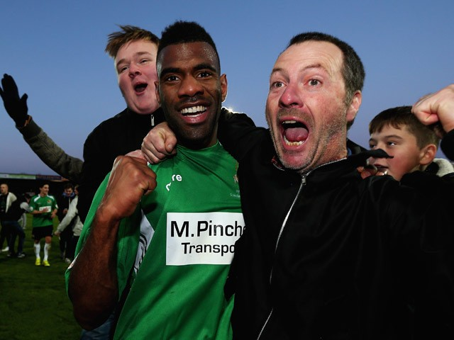 Daniel Ntl of Worcester City celebrates his teams draw with supporters after the FA Cup Second Round match between Scunthorpe United and Worcester City at Glanford Park on December 7, 2014