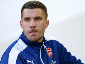 Lukas Podolski of Arsenal takes his seat on the bench before the Barclays Premier League match between West Ham United and Arsenal at Boleyn Ground on December 28, 2014