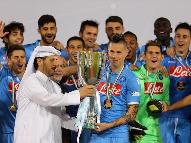Qatar's Prime Minister, Sheikh Abdullah bin Nasser bin Khalifa al-Thani (L) presents Napoli's Slovak midfielder and captain Marek Hamsik (C) with Italian Super Cup trophy on December 22, 2014