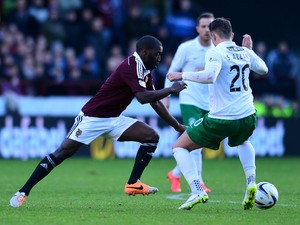 Morgaro Gomis of Hearts is tackled by Danny Handling of Hibernian during the Scottish Championship match between Heart of Midlothian F.C. and Hibernian F.C. at Tynecastle Stadium on January 3, 2015