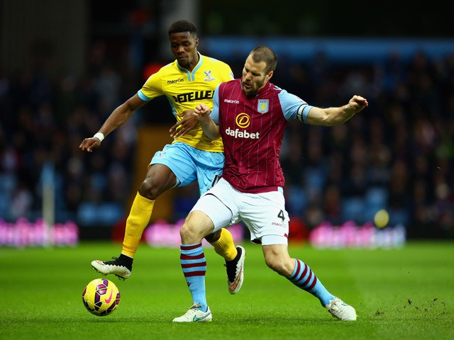 Wilfried Zaha of Crystal Palace and Ron Vlaar of Aston Villa battle for the ball during the Barclays Premier League match between Aston Villa and Crystal Palace at Villa Park on January 1, 2015