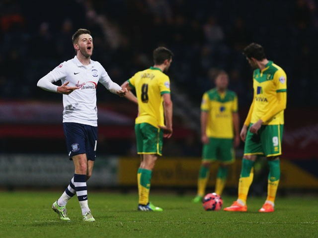 Despair for Norwich City players as Paul Gallagher of Preston North End (L) celebrates scoring their first goal during the FA Cup Third Round match between Preston North End and Norwich City at Deepdale on January 3, 2015
