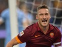 Caption:Roma's forward Francesco Totti celebrates after scoring during the Italian Serie A football match on January 11, 2015