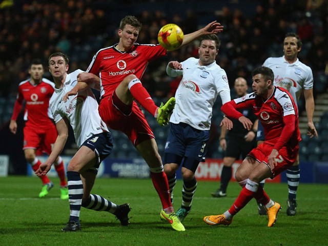 Paul Downing of Walsall clears the ball under pressure from Paul Huntington of Preston North End during the Johnstone's Paint Northern Area Final, First Leg match between Preston North End and Walsall at Deepdale on January 7, 2015