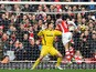 Arsenal's French defender Laurent Koscielny heads the opening goal past Stoke City's Bosnian goalkeeper Asmir Begovic during the English Premier League football match between Arsenal and Stoke City at the Emirates Stadium in London on January 11, 2015