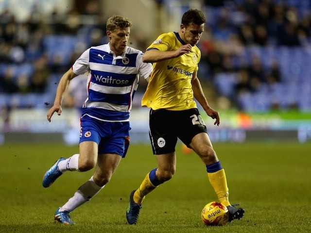 Reading's Pavel Pogrebnyak chases after Wigan's Jason Pearce on February 17, 2015
